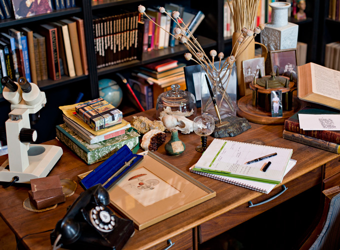 Personal objects sit atop the desk in the library.