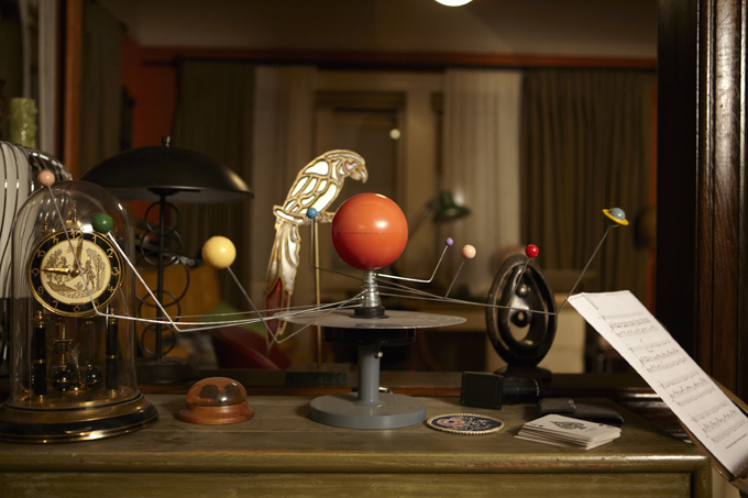 A model of the solar system, sheet music, playing cards, a brass bird  and, of course, more clocks on a shelf between the living room and dining room hint at the hobbies of lone wolf, Monroe.